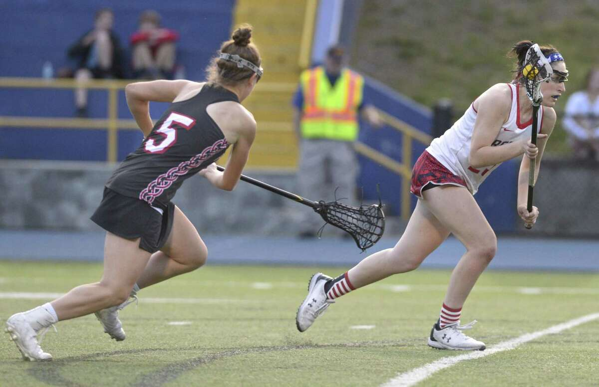 New Fairfield's Reagan Tenaglia (23) stays ahead of Pomperaug's Maddie Villa (5) to get to the goal and score the game winning goal in the SWC girls lacrosse championship game between Pomperaug and New Fairfield high schools. Wednesday evening, May 22, 2019, at Newtown High School, Newtown, Conn.