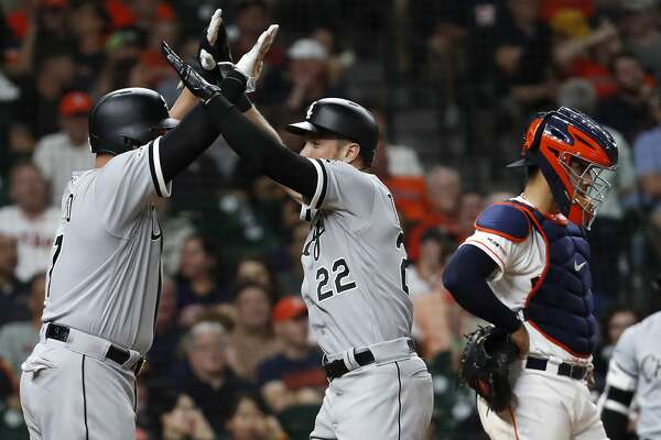 Chicago White Sox Charlie Tilson (22) high fives Yonder Alonso (17) as they celebrate Tilson's grand slam home run off reliever Josh James during the sixth inning of a major league baseball game at Minute Maid Park on Wednesday, May 22, 2019, in Houston.