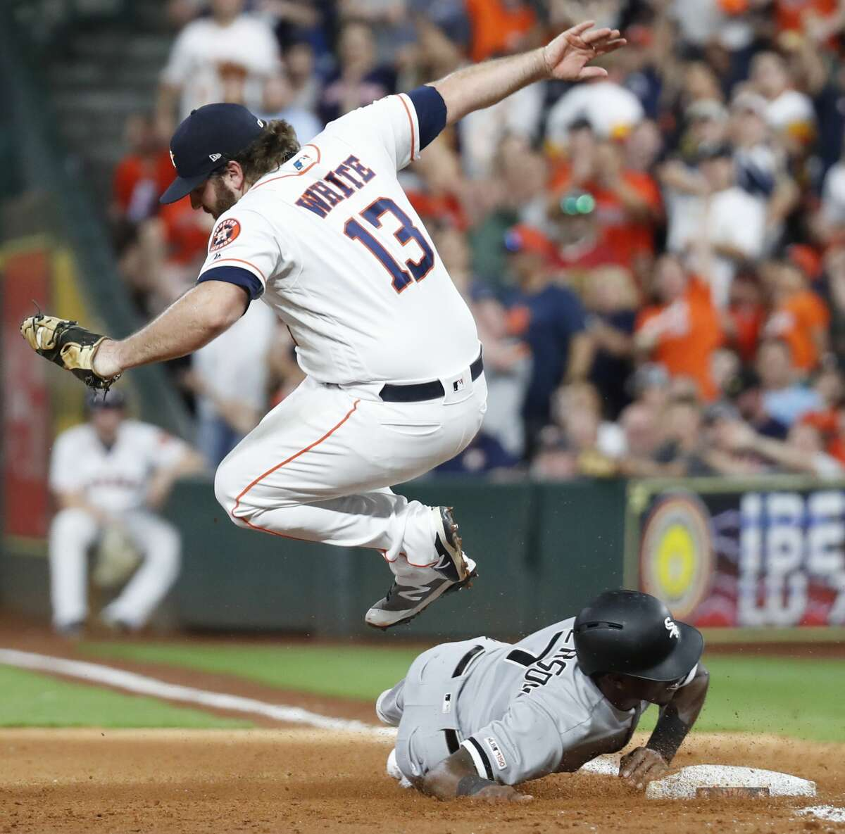 Houston Astros designated hitter Tyler White (13) leaps over Chicago White Sox Tim Anderson (7) after completing a double play on a throw from left field from Jake Marisnick during the fifth inning of a major league baseball game at Minute Maid Park on Wednesday, May 22, 2019, in Houston.
