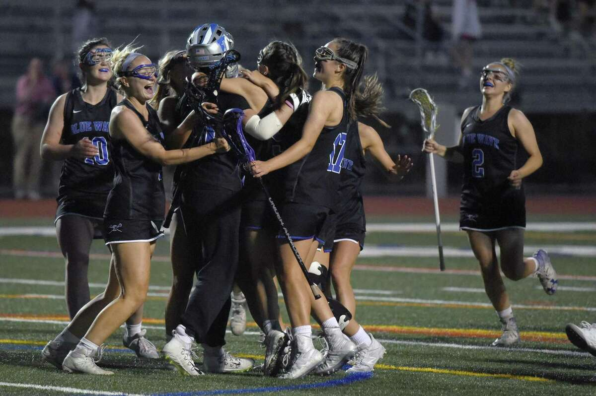 The Darien Blue Wave celebrates after defeating New Canaan 12-7 for the FCIAC girls lacrosse championship at Testa Field in Norwalk on Wednesday, May 22, 2019.