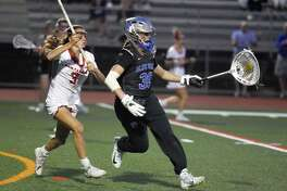 Darien's Shea Dolce (30) escapes from New Canaan's Dillyn Patten (3) during the FCIAC girls lacrosse championship on Wednesday.
