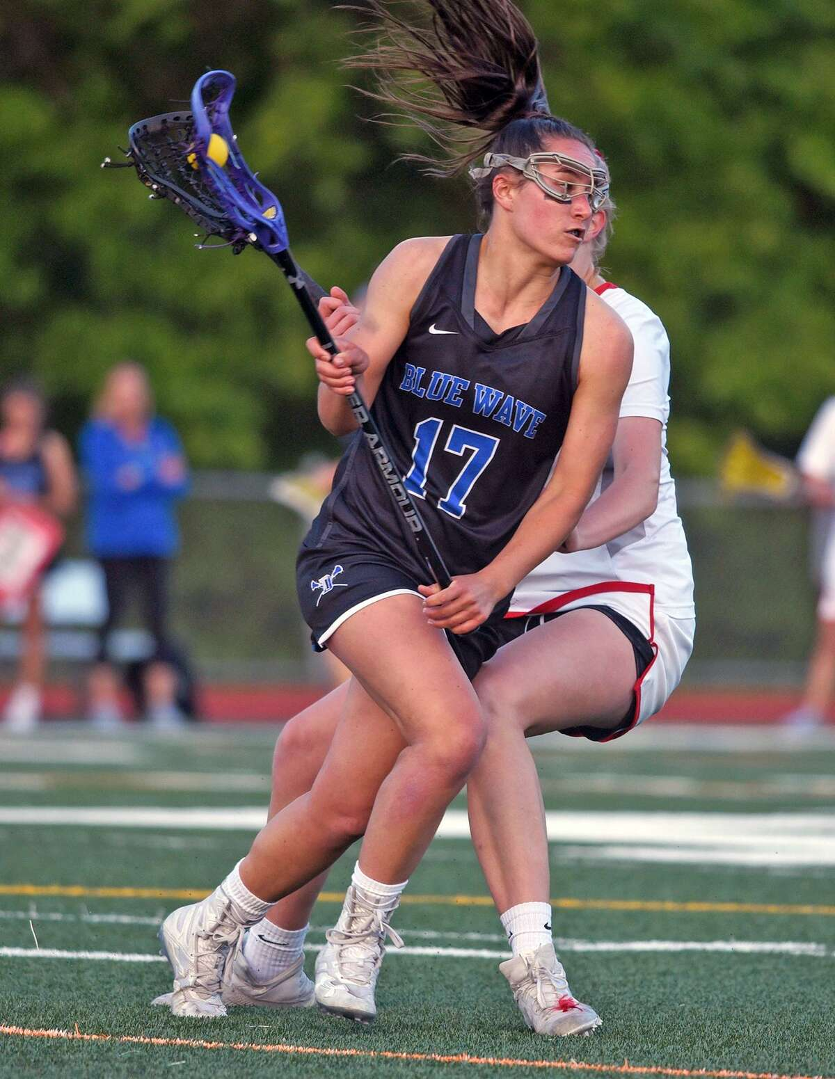 Darien's Sarah Jaques (17) drives past a New Canaan Ram during the FCIAC girls lacrosse championship at Testa Field in Norwalk on Wednesday, May 22, 2019.