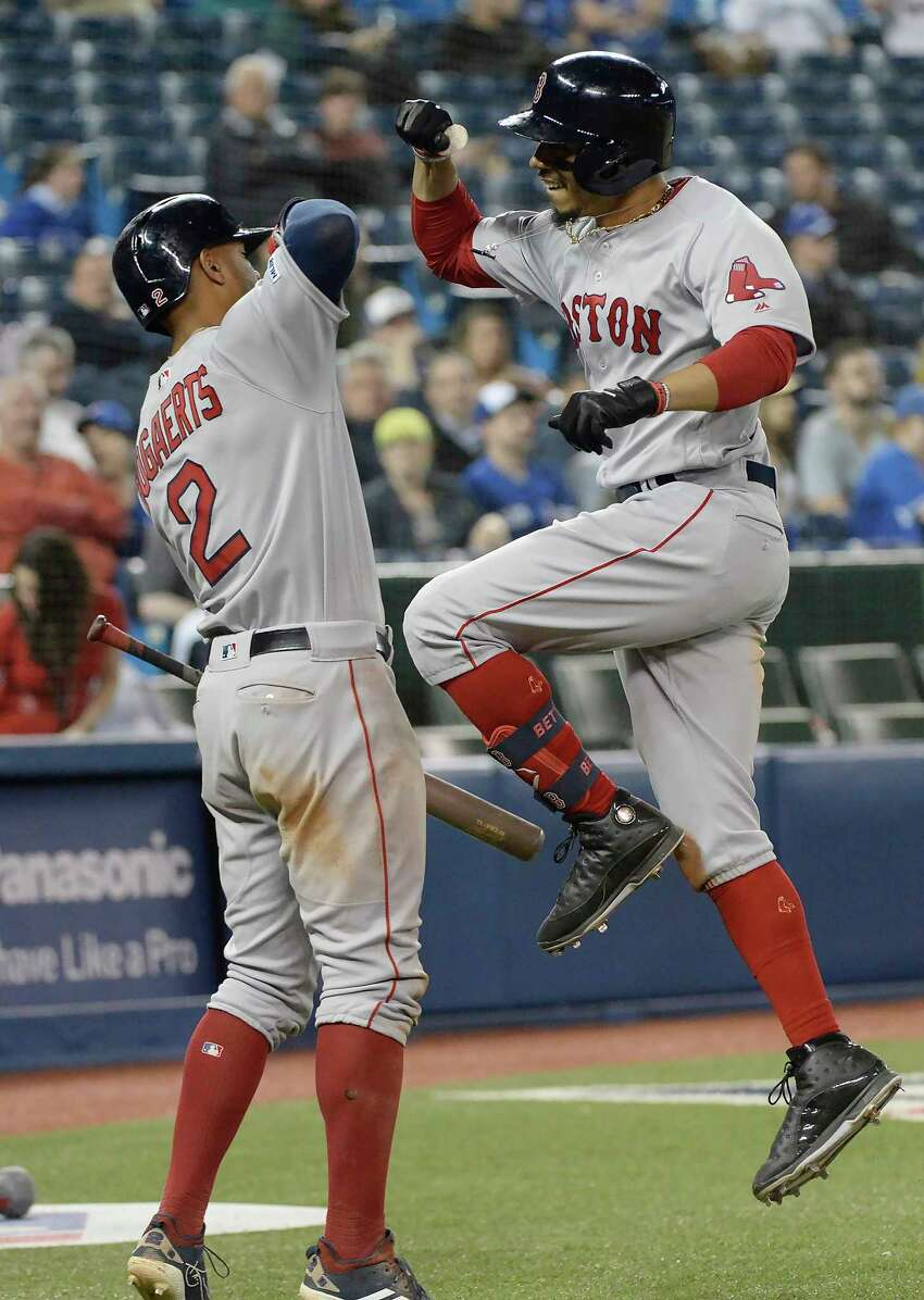 Boston Red Sox's Mookie Betts, right, celebrates his home run with Xander Bogaerts during the 12th inning of a baseball game against the Toronto Blue Jays on Wednesday, May 22, 2019, in Toronto. (Nathan Denette/The Canadian Press via AP)