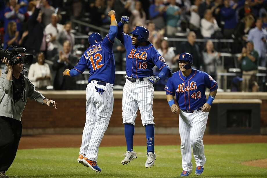 The Mets' Rajai Davis (18) celebrates his home run with teammates Juan Lagares and Wilson Ramos. Photo: Michael Owens / Getty Images