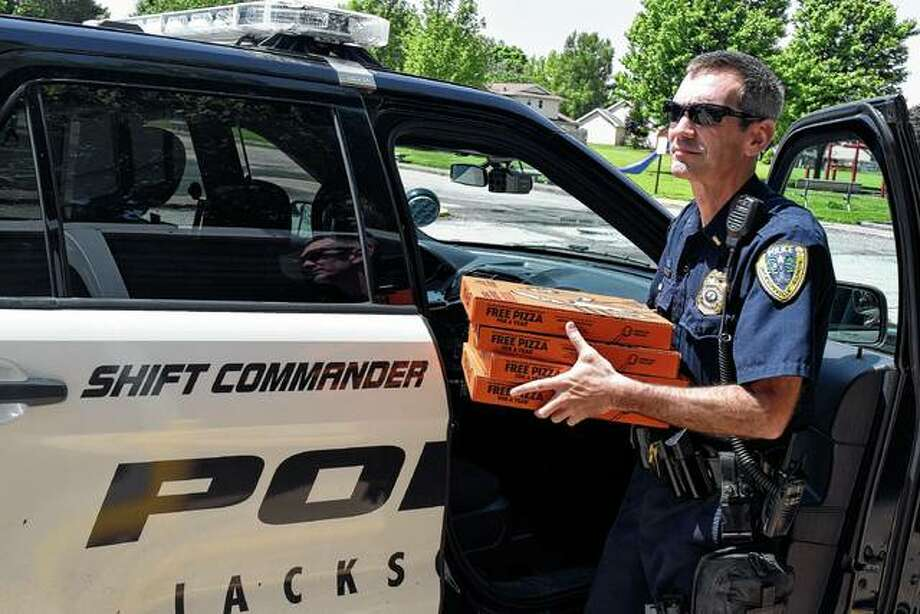 Jacksonville Police Lt. Sean Walker delivers pizza Wednesday to Shanon Keller's fifth-grade class at Eisenhower Elementary School's after fifth-grader Emalee Pool won first place in the National Police Week Citywide Fifth-Grade Essay Contest.