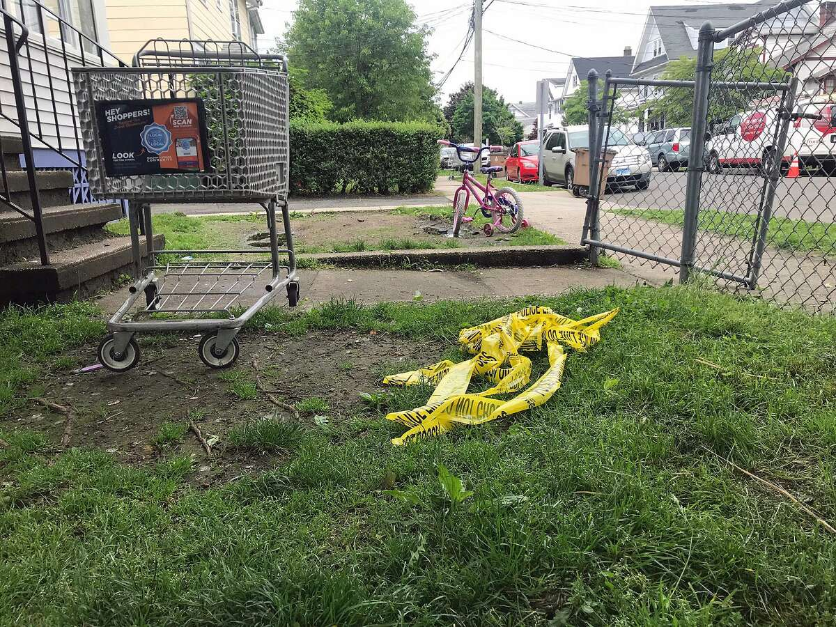 A child's bicycle stands next to discarded police caution tape at a Stamford residence on Frederick Street where a man was killed on Wednesday, May 21, 2019.