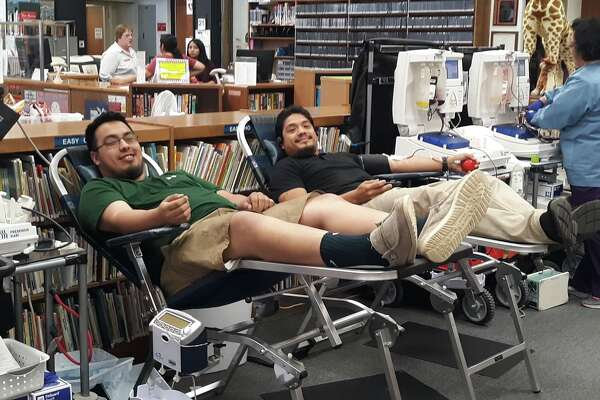Luis Gonzales (on the left) and Rocky Rosas (on the right) give blood during the biannual Vitalant Blood Systems drive at the Unger Memorial Library on Tuesday.