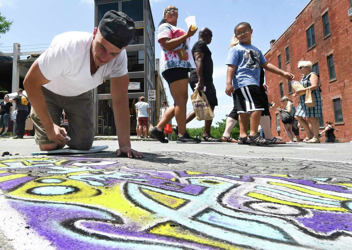Dominic Patalino of Green Island, N.Y., works on a abstract chalk drawing during Troy River Fest Saturday, June 16, 2018, in Troy, N.Y. (Hans Pennink / Special to the Times Union)