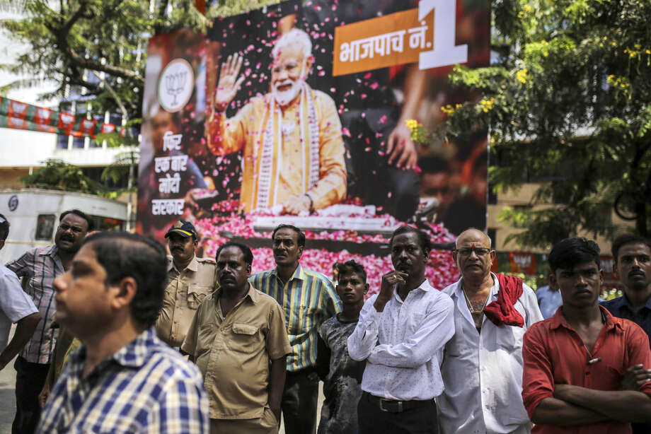 People gather in front of a banner featuring an image of Indian Prime Minister Narendra Modi outside a Bhartiya Janata Party (BJP) state office in Mumbai, India, on May 23, 2019. Photo: Bloomberg Photo By Dhiraj Singh. / © 2019 Bloomberg Finance LP