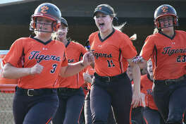 Edwardsville's Ellie Viox scores on Katherine Bobinski-Boyd's walk-off homer as teammates rush out of the dugout to celebrate.