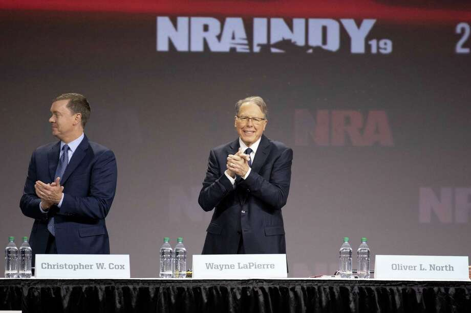 Wayne LaPierre, chief executive officer of the National Rifle Association (NRA) ( right) and Chris Cox, chief lobbyist of the NRA, stand near an empty seat reserved for retired U.S. Marine Corps Lieutenant Colonel Oliver North, president of the NRA, at the NRA annual meeting of members in Indianapolis on April 27, 2019. Photo: Bloomberg Photo By Daniel Acker. / © 2019 Bloomberg Finance LP