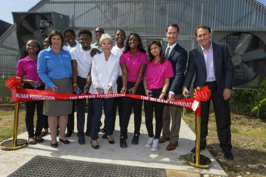 Students and administrators join Janice McNair(center)at a celebratory ribbon cutting for the completion of Pro-Vision's expansion funded by a $450,000 gift from The Robert and Janice McNair Foundation. Two aquaponic greenhouses on the two-acre working urban farm on the school's campus will connect students of the charter school with farms, farmers and the community through entrepreneurial endeavors tied to sustainable health and agricultural practices. Also pictured are Kristi Cooper, executive director of The Robert and Janice McNair Foundation, Roynell Young, Pro-Vision founder and CEO, Holt McNair andAlan Hassenflu, Board Chairman, Pro-Vision, Inc. Photo: Courtesy Photo By Hugh Hargrave