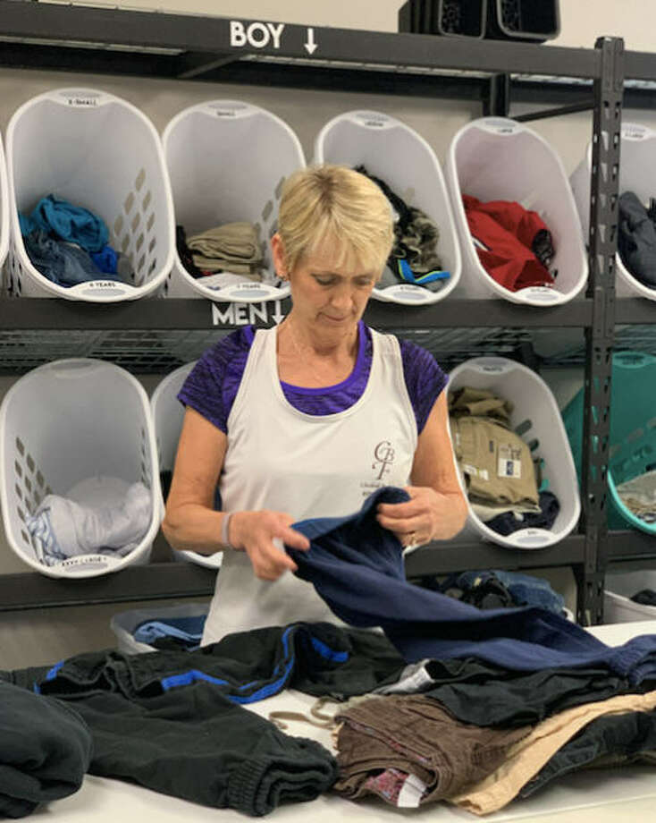 A volunteer at Clothed by Faith sorts donated boys clothing. The nonprofit has put out a call for shorts, jeans and T-shirts for men and youths ages 12 and older. Photo: Clothed By Faith
