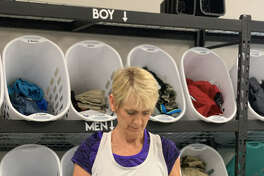 A volunteer at Clothed by Faith sorts donated boys clothing. The nonprofit has put out a call for shorts, jeans and T-shirts for men and teens.