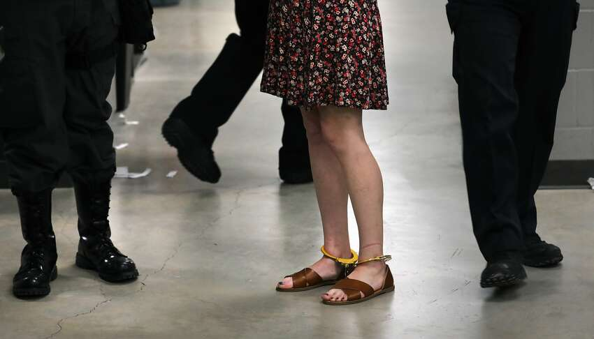 A woman in ankle cuffs in the intake area at the Bexar County Detention Center, on Thursday, May 9, 2019.