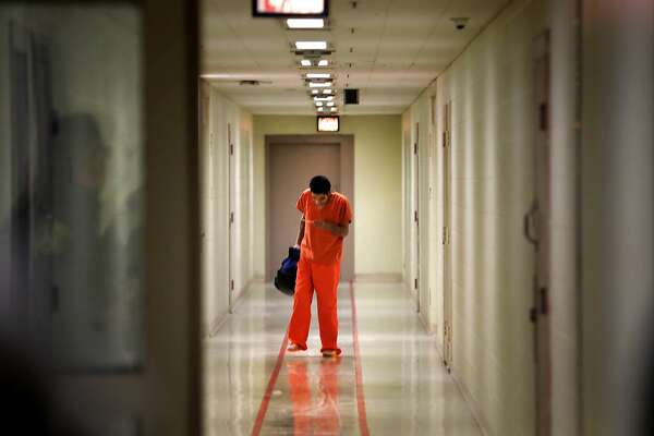 An inmate at the Bexar County Detention Center reads a pass as he walks down a hallway, on Thursday, May 9, 2019.