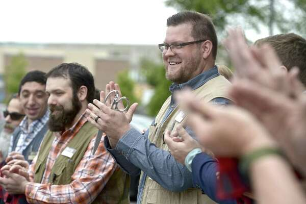 Sam Reynolds, store manager of the new Duluth Trading Co store in the Shops at Marcus Dairy shopping center, joins employees in a ribbon cutting ceramony for the new store on Thursday, May 23, 2019, in Danbury, Conn,