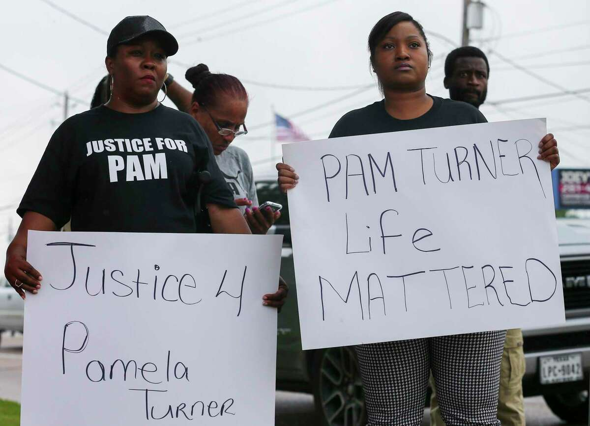 Kendra Riley, left, and T.J. Johnson hold up signs asking for justice on behalf of their late aunt, Pamela Turner, during a demonstration by the Black Lives Matter Houston group outside the Baytown Police Department Saturday, May 18, 2019, in Baytown, Texas. Turner was fatally shot during a confrontation with Baytown Police officer Juan Delacruz at The Brixton Apartments complex, where she lived.