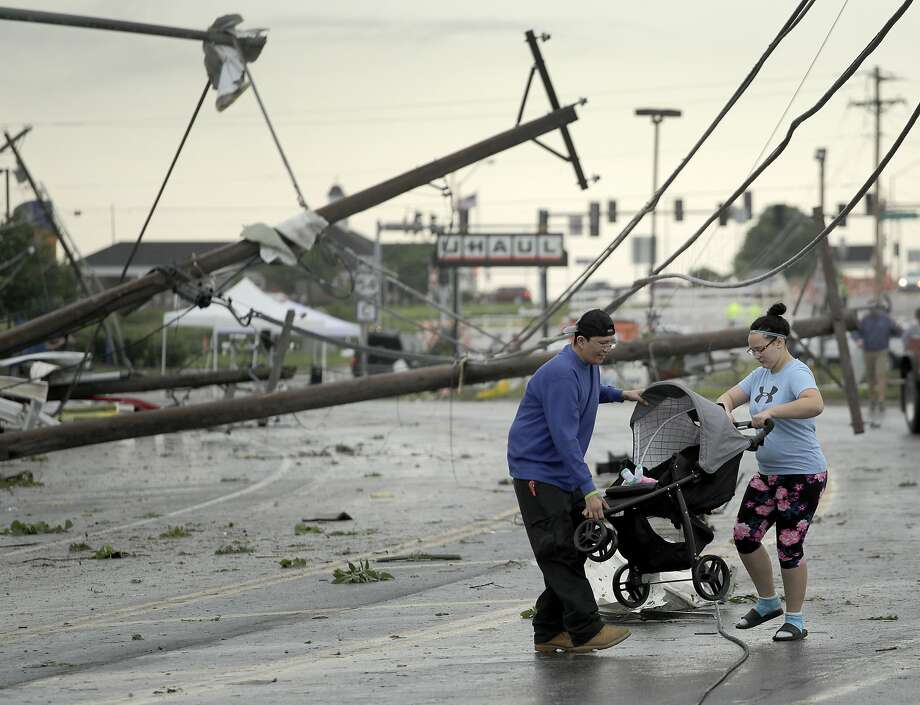 Ray Arellana and Jessica Rodgers carry Rodgers' sister Sophia after a tornado tore apart buildings in Jefferson City, Mo. Photo: Charlie Riedel / Associated Press