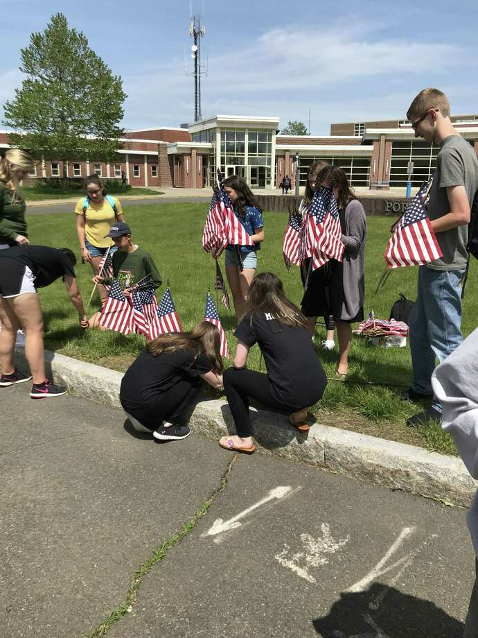 Flags are being placed at Portland High School to remember Connecticut residents killed in Iraq and Afghanistan. Photo: Jeff Mill / Hearst Connecticut Media