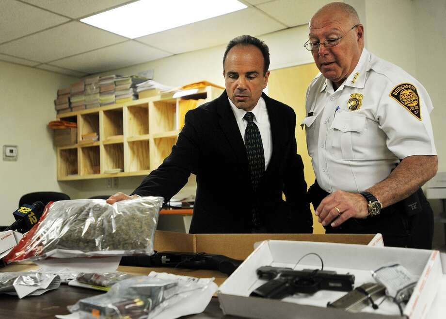 Bridgeport Mayor Joe Ganim and Police Chief A.J. Perez show heroin, marijuana, guns, and cash seized following the arrest of three men, including Black Rock resident Joel Jean, Wednesday evening. Jean is suspected of distributing heroin throughout the city of Bridgeport as well as the towns of lower Fairfield County. The Darien Police Department Selective Enforcement Unit worked with the Bridgeport Narcotics Task Force on the investigation. Photo: Brian A. Pounds / Hearst Connecticut Media / Connecticut Post