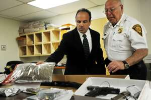 Bridgeport Mayor Joe Ganim and Police Chief A.J. Perez show heroin, marijuana, guns, and cash seized following the arrest of three men, including Black Rock resident Joel Jean, Wednesday evening. Jean is suspected of distributing heroin throughout the city of Bridgeport as well as the towns of lower Fairfield County. The Darien Police Department Selective Enforcement Unit worked with the Bridgeport Narcotics Task Force on the investigation.