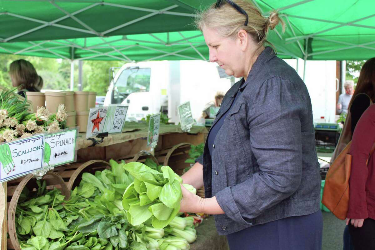 Darien resident Joanne Moore shops for bok choy at the Fort Hills Farm stall at the Westport Farmers Market on May 23, 2019. Moore says she goes to the market every year and tries to lead a healthy lifestyle.
