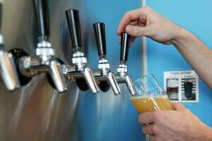 """John Holler pours """"Won't You Be My Neighbor"""" at the Holler Brewery taproom in Sawyer Yards. Holler, who was inegral in the push to legalize beer-to-go in Texas, said he still can't believe he'll legally be able to sell cans of his brews come Sunday."""