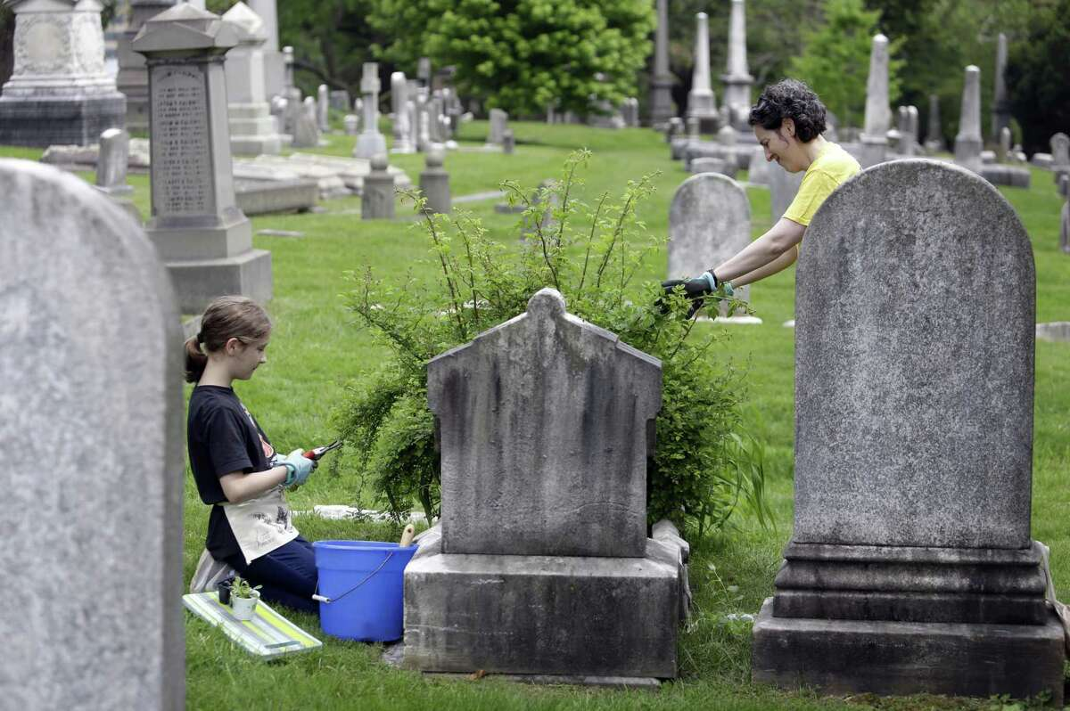 Celina Gray, right, and her daughter Kalliope Kourelis, trim a rose bush growing on the cradle grave of Mary Glenn, at the Woodlands Cemetery, Saturday May 4, 2019 in Philadelphia. The cemeteries of yore existed as much the living as for the dead. And a handful of these 19th century graveyards are restoring the bygone tradition of cemetery gardening. (AP Photo/Jacqueline Larma)