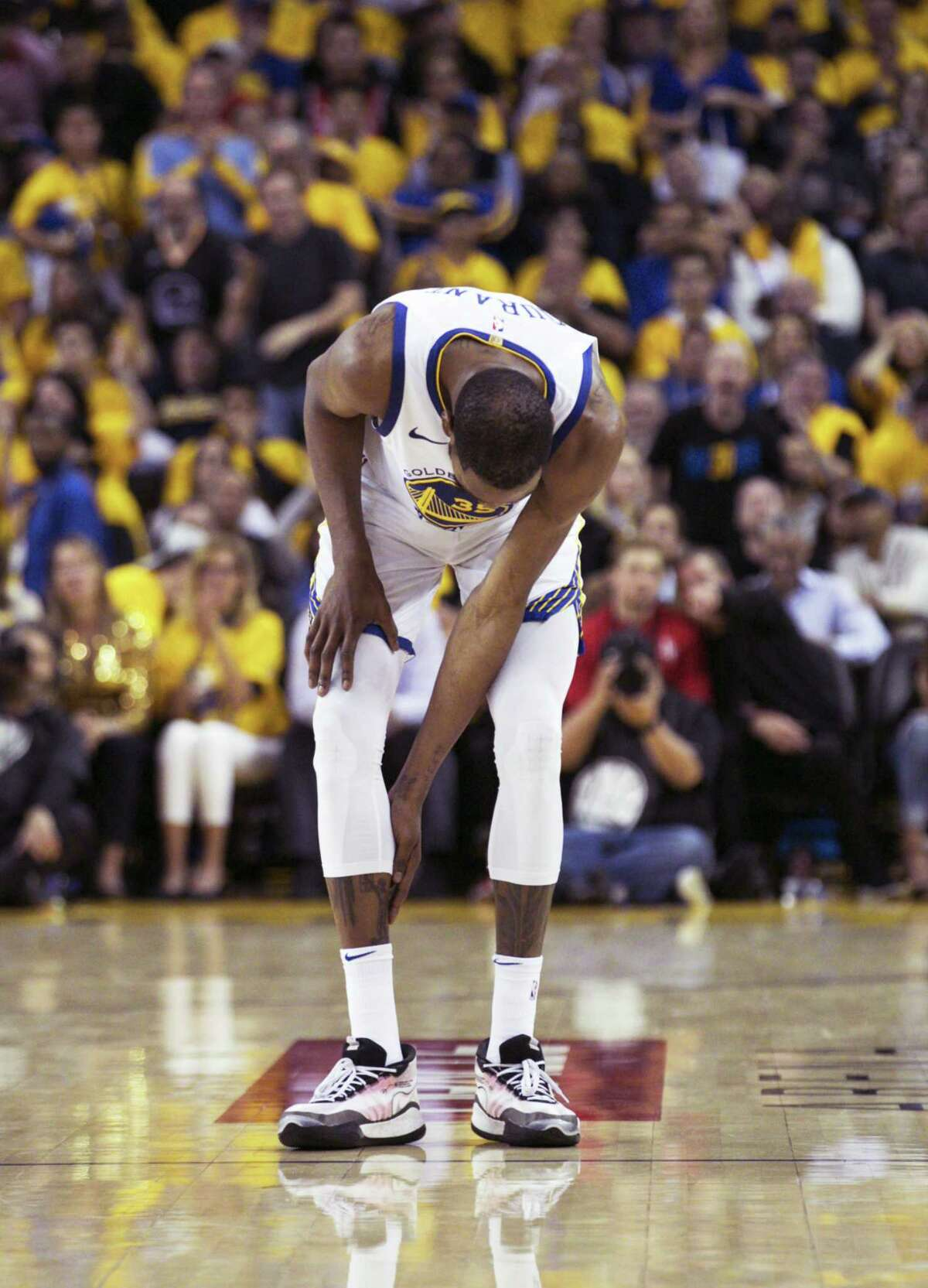 Golden State Warriors Kevin Durant checks his calf in the third quarter during game 5 of the Western Conference Semifinals between the Golden State Warriors and the Houston Rockets at Oracle Arena on Wednesday, May 8, 2019 in Oakland, Calif.