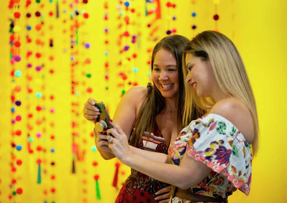 Clarissa Rodriguez, an event coordinator with Extraordinary Events, looks at a photo with Angelina Rouget, a market and promotions coordinator at Univision, during a media preview at a new interactive pop-up photo studio inside Univision's building on the Southwest Freeway, Thursday, May 23, 2019.