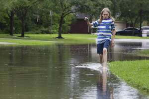 Lane Fisher explores a flooded street near his house in Kingwood as heavy rains soak Greater Houston, Friday, May 3, 2019.