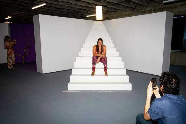 David Serna, who works at Univision and helped put together two of the installations, photographs Clarissa Rodriguez at the new interactive pop-up photo studio inside Univision's building on the Southwest Freeway, Thursday, May 23, 2019.
