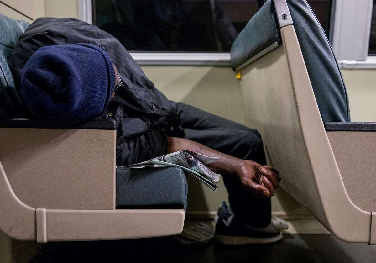A homeless man sleeps on the back of a BART train en route to the West Oakland BART Station in Oakland, Calif. Thursday, May 23, 2019.