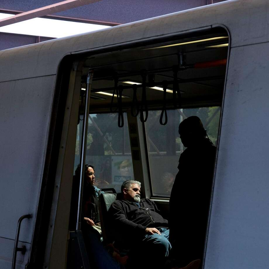 A man sleeps in the sunlight while on an idle train at MacArthur BART Station in Oakland, Calif. Thursday, May 23, 2019. BART police will be handing out index cards this week to encourage people to secure their personal electronic devices. Click through the gallery for a look at offenses that can get you banned from BART. Photo: Jessica Christian, The Chronicle