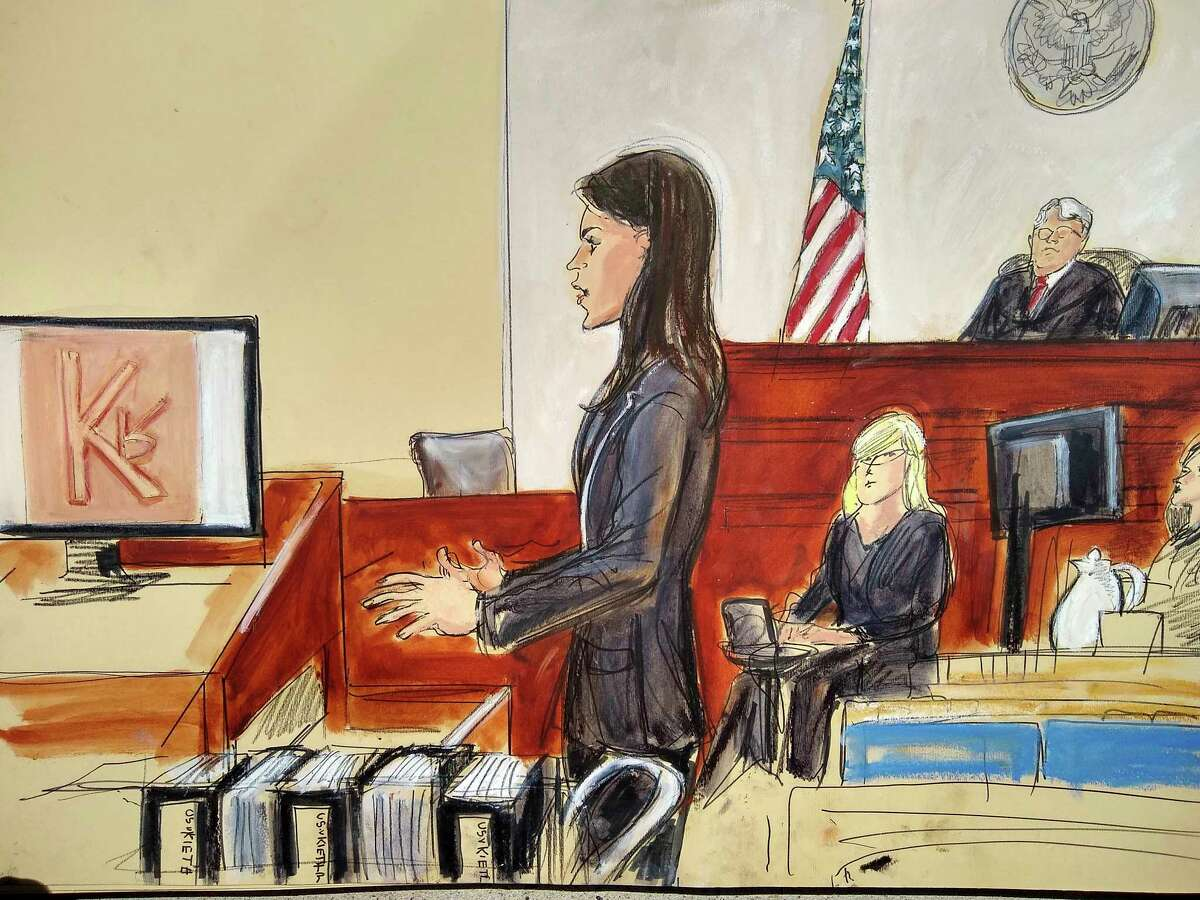 In this courtroom drawing, Assistant US Attorney Tanya Hajjar, left, gives opening statement to jury as Judge Nicholas Garaufis listens from the right, in the sex trafficking trial of NXIVM group leader Keith Raniere, Tuesday, May 7, 2019 in New York. The image on the left side screen is a photo of the branded mark made on a woman with Raniere's initials.