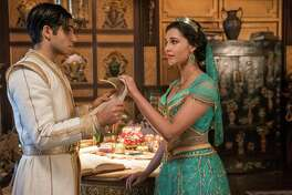 """This image released by Disney shows Mena Massoud as Aladdin, left, and Naomi Scott as Jasmine in Disney's live-action adaptation of the 1992 animated classic """"Aladdin."""" (Daniel Smith/Disney via AP)"""