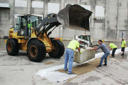 Alton Public Works Department employees rebuild the flood wall at the intersection of Broadway and State streets Thursday morning. The latest predictions call for a crest at Alton of 35.4 feet, which would be the fifth highest recorded crest.
