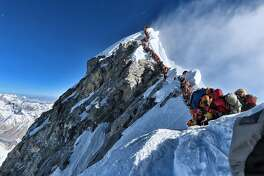 """This handout photo taken on May 22, 2019 and released by climber Nirmal Purja's Project Possible expedition shows heavy traffic of mountain climbers lining up to stand at the summit of Mount Everest. - Many teams had to line up for hours on May 22 to reach the summit, risking frostbites and altitude sickness, as a rush of climbers marked one of the busiest days on the world's highest mountain. (Photo by Handout / Project Possible / AFP) / RESTRICTED TO EDITORIAL USE - MANDATORY CREDIT """"AFP PHOTO / PROJECT POSSIBLE"""" - NO MARKETING NO ADVERTISING CAMPAIGNS - DISTRIBUTED AS A SERVICE TO CLIENTS ---HANDOUT/AFP/Getty Images"""