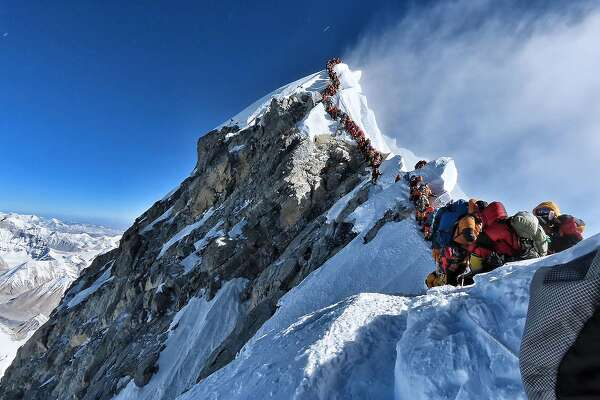 "This handout photo taken on May 22, 2019 and released by climber Nirmal Purja's Project Possible expedition shows heavy traffic of mountain climbers lining up to stand at the summit of Mount Everest. - Many teams had to line up for hours on May 22 to reach the summit, risking frostbites and altitude sickness, as a rush of climbers marked one of the busiest days on the world's highest mountain. (Photo by Handout / Project Possible / AFP) / RESTRICTED TO EDITORIAL USE - MANDATORY CREDIT ""AFP PHOTO / PROJECT POSSIBLE"" - NO MARKETING NO ADVERTISING CAMPAIGNS - DISTRIBUTED AS A SERVICE TO CLIENTS ---HANDOUT/AFP/Getty Images"