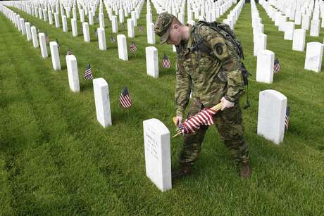 "Army Cpl. Matthew Munie, of Jackson, Mich., and a member of the 3d U.S. Infantry Regiment also known as The Old Guard, places flags in front of a headstone for ""Flags-In"" at Arlington National Cemetery in Arlington, Va., Thursday, May 23, 2019, to honor the nation's fallen military heroes."