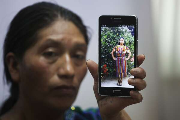 FILE - In this Friday, May 25, 2018, file photo, Dominga Vicente shows a photo of her niece, 20-year-old Claudia Patricia Gomez Gonzalez, who was allegedly killed by an agent of the U.S. Border Patrol in Nuevo Laredo, Texas, during a news conference at the National Migrants Commission headquarters in Guatemala City. Advocates for Gomez Gonzalez are demanding $100 million in damages. (AP Photo/Moises Castillo, File)