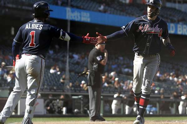 Atlanta Braves' Dansby Swanson, right, is congratulated by Ozzie Albies (1) after scoring against the San Francisco Giants during the 13th inning inning of a baseball game Thursday, May 23, 2019, in San Francisco. Swanson scored on a single by Austin Riley. (AP Photo/Ben Margot)