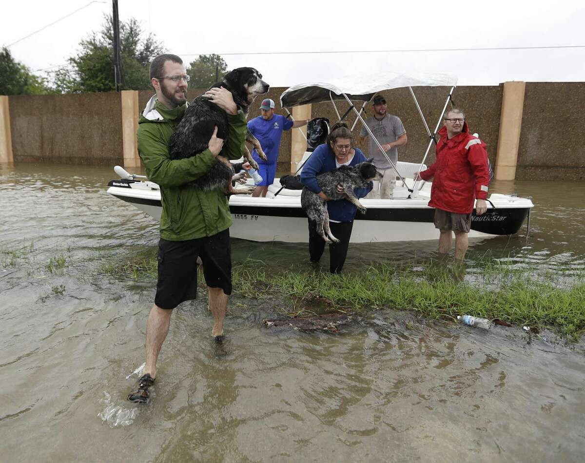 Shelly Jones gets help carrying her dogs out of the boat belonging to Josh Mtanyos, with the Cajun Navy, as they were rescued as heavy rains from Tropical Storm Harvey continued filling the the San Jacinto River, just north of 1960, Tuesday, Aug. 29, 2017, in Houston. ( Karen Warren / Houston Chronicle )