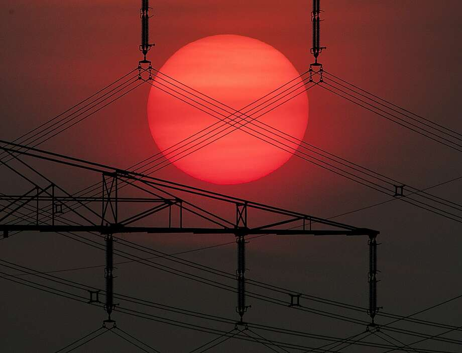 The sun rises behind an electrical power line in Frankfurt, Germany, Thursday, May 23, 2019. (AP Photo/Michael Probst) Photo: Michael Probst, Associated Press
