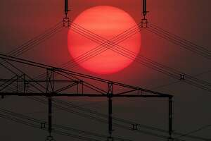 The sun rises behind an electrical power line in Frankfurt, Germany, Thursday, May 23, 2019. (AP Photo/Michael Probst)