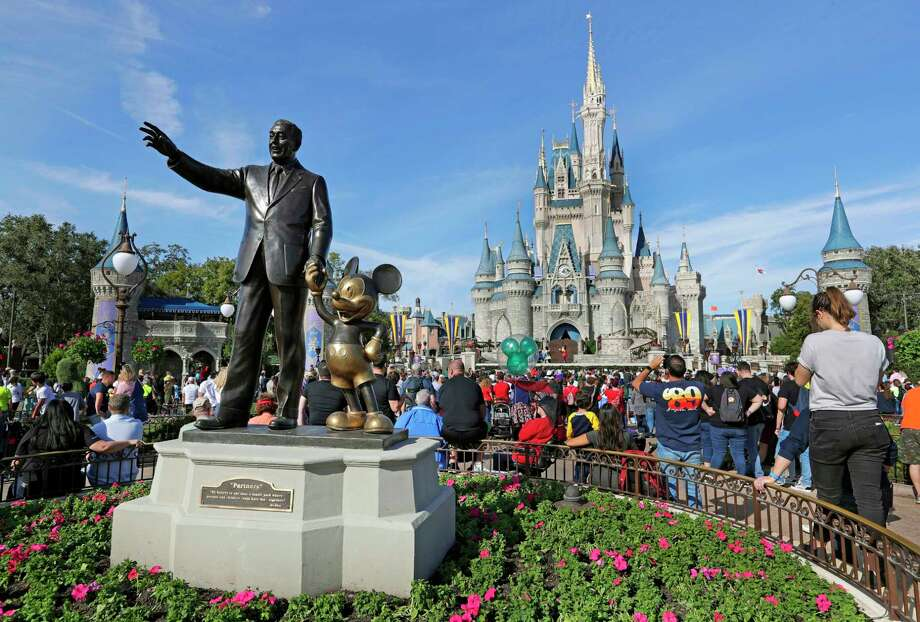 FILE - In this Jan. 9, 2019 file photo, guests watch a show near a statue of Walt Disney and Micky Mouse in front of the Cinderella Castle at the Magic Kingdom at Walt Disney World in Lake Buena Vista, part of the Orlando area in Fla. Magic Kingdom was the best-attended park in 2018 with 20.8 million visitors, followed by Disneyland in California with 18.6 million visitors. (AP Photo/John Raoux, File) Photo: John Raoux / Copyright 2019 The Associated Press. All rights reserved