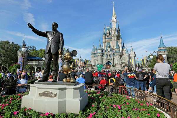 FILE - In this Jan. 9, 2019 file photo, guests watch a show near a statue of Walt Disney and Micky Mouse in front of the Cinderella Castle at the Magic Kingdom at Walt Disney World in Lake Buena Vista, part of the Orlando area in Fla. Magic Kingdom was the best-attended park in 2018 with 20.8 million visitors, followed by Disneyland in California with 18.6 million visitors. (AP Photo/John Raoux, File)