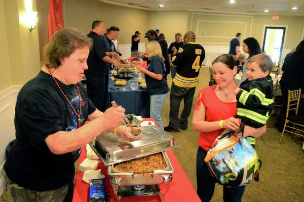 Stephanie King, of Norwalk, gets some chili with her son Kaden, 2, from TJ Baker, with CT Firefighters Charitable Foundation's chili stand during the Bridgeport Firefighter's Local 834 and CT Friends of Phoenix 1st Annual Chili Cook-off at Vazzano's Four Seasons in Stratford, Conn., on Thursday May 23, 2019. Fire departments from all over the state presented their best chili creations for one to be chosen as People's Choice. All proceeds go directly to the CT Friends of Phoenix Burn SOAR (Survivors Offering Assistance in Recovery®) program out of the CT Burn Center at Bridgeport Hospital.