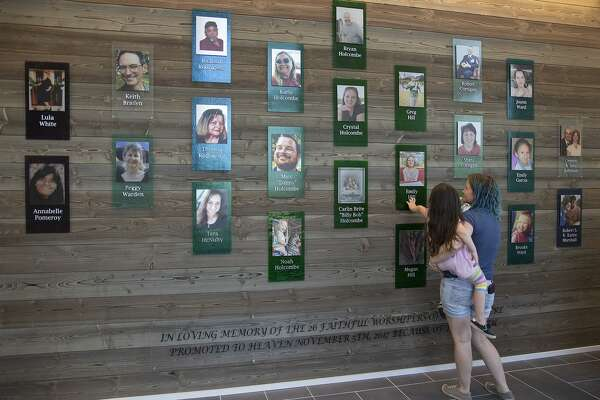 Sarah Slavin and her daughter, Elene, look at the photos of their family, the Holcombes and the Hills, and the others lost at their church, in the memorial tower in the new building for First Baptist Church of Sutherland Springs on Friday, May 17, 2019.